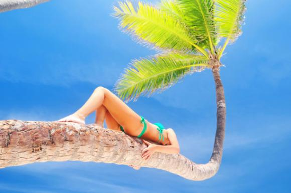 Frau liegt auf einer Palme – Mexiko