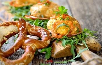 Bayerischer Obazter auf Rucolablättern mit Papikazwiebelringen und Brezel serviert
