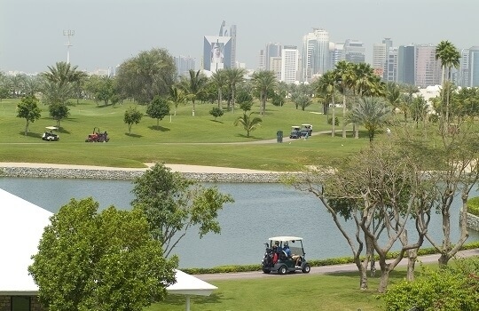 Blick auf ein fahrendes Golf Caddy durch eine Anlage, im Hintergrund Dubai