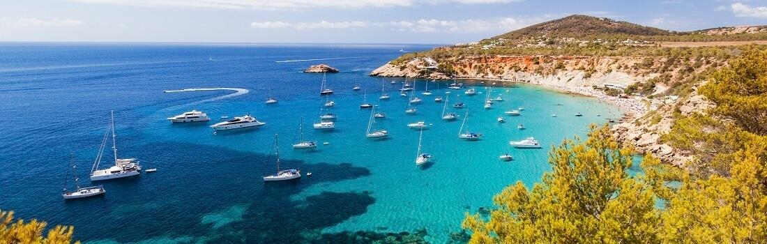 Blick auf eine Bucht mit Booten und azurblauen Meer, Ibiza