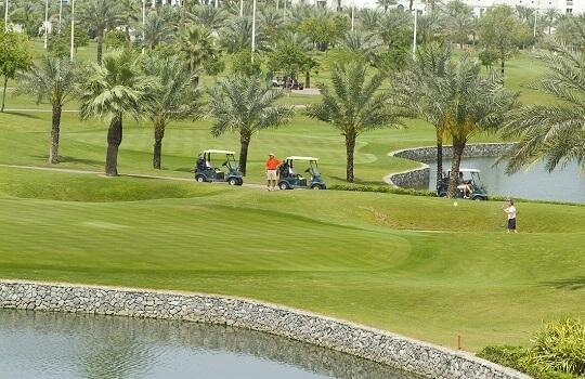 Blick auf eine Golfanlage in Dubai, zu sehen sind Golfer und Caddys