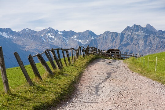 Wanderweg mit Holzzaun und Bergpanorama in Südtirol
