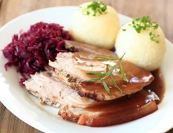 Ein Teller mit Schweinekrustenbraten, Knödeln und Rotkohl in einem Restaurant am Titisee, Deutschland