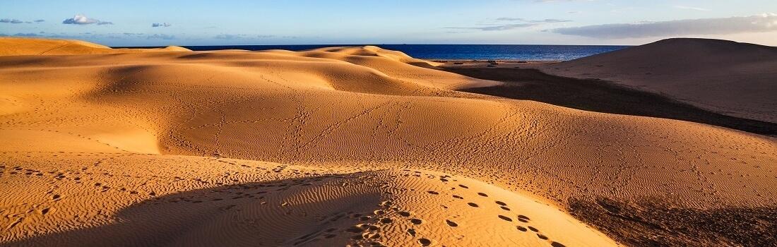 Fußspuren in den Dünen von Maspalosmas, im Hintergrund das Meer