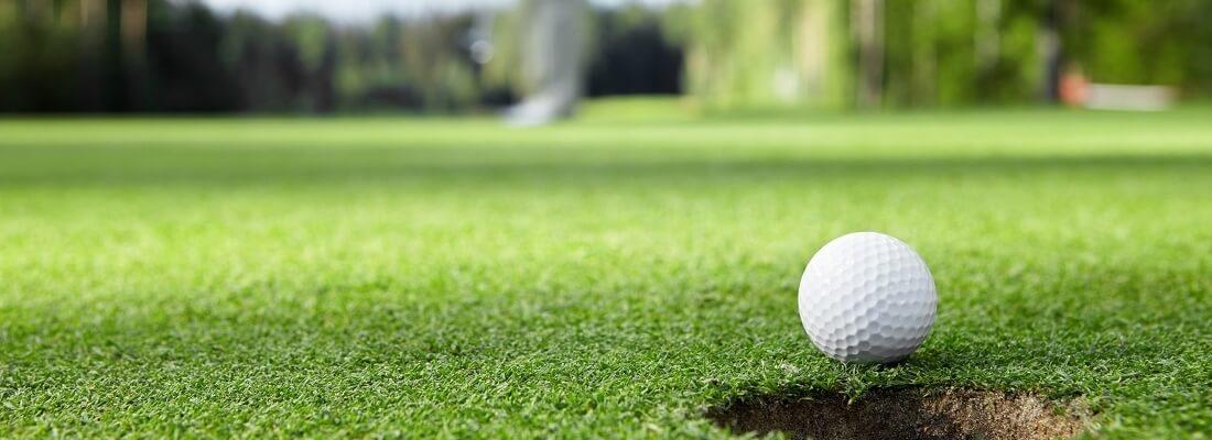 Golfball vor dem Loch, Bokeh Bild, Golfball scharf, Hintergrund verschwommen