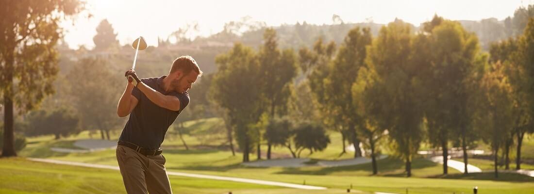 Golfer beim Abschlag, Golfplatz im Sonnenuntergang