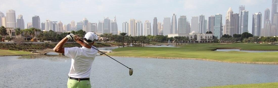 Golfer beim Abschlag, Im Hintergrund die Skyline von Dubai