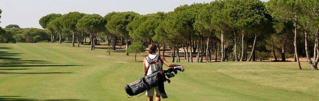 Golferin mit Golfbag auf dem Fairway