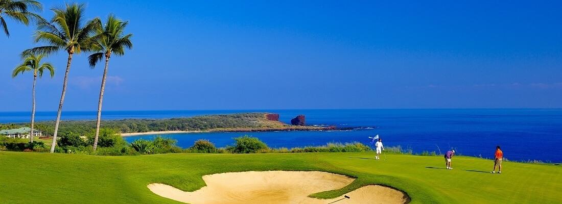 Golfplatz an der Küste, Golfer auf dem Grün, Palmen im Hintergrund