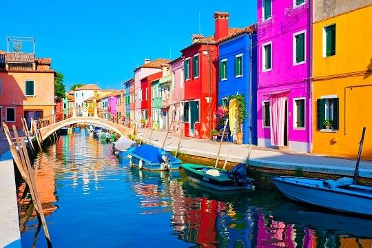 Bunte Häuser an einem Kanal mit Gondeln in Venedig, Italien