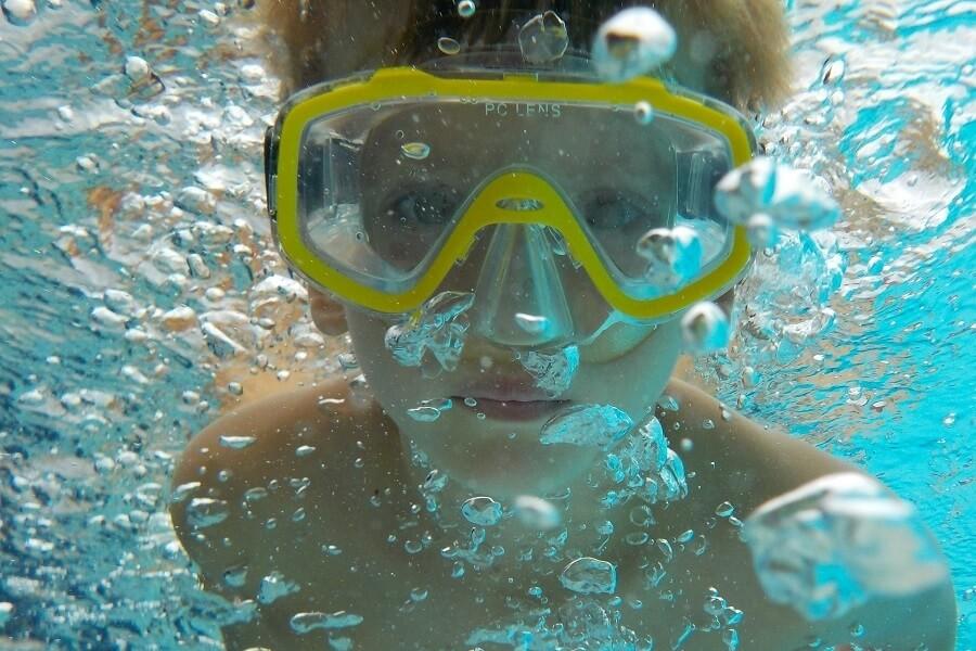 Kind mit Taucherbrille unter Wasser, Badeurlaub