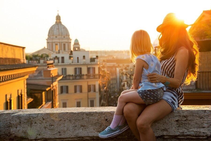Mutter mit Tochter sitzen auf Mauer und schauen auf italienische Stadt, Venedig
