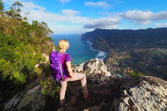 Frau beim Wandern in den Bergen Madeiras mit Blick auf die Küste, Portugal