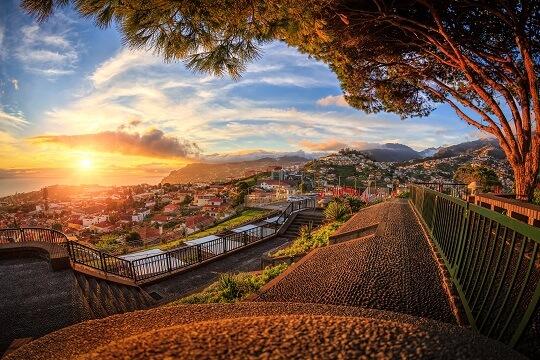 Blick vom Berg auf ein Dorf auf Madeira zum Sonnenuntergang, Portugal