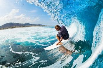 Surfer reitet eine türkis blaue Welle am Strand von Portugal