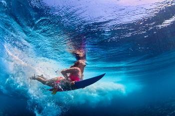 Surferin im Bikini taucht mit Surfbrett unter, Portugal