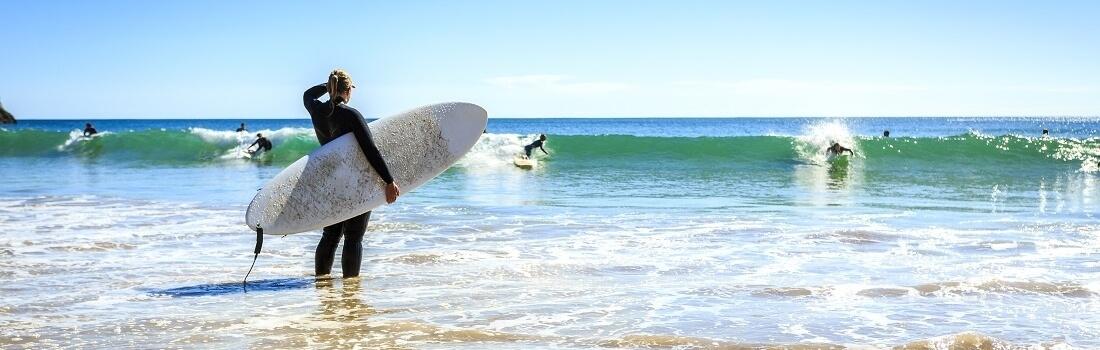 Surfer am Wellenreiten an der Algarve, Surfer schaut anderen beim surfen zu, Portugal