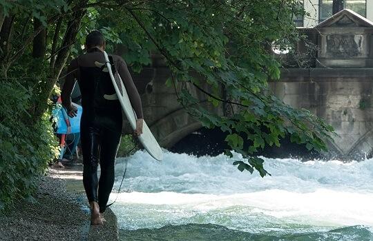Surfer am rand des Eisbachs mit Surfbrett unter dem Arm, München