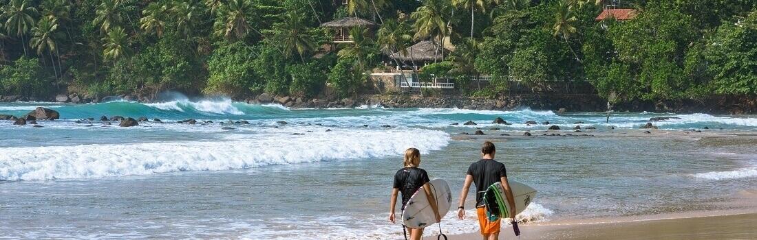 Surfer am weißen Strand in der Bucht von Mirissa, Sri Lanka