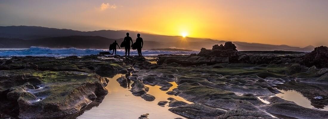 Surfer im Sonnenuntergang schauen auf das Meer, El Confital beach, Gran Canaria