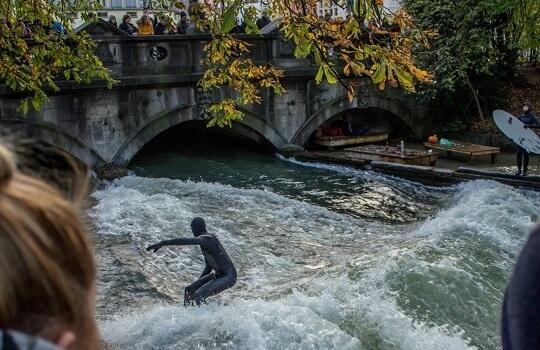 Surfer reitet Wellen im Eisbach in richtung Brücke, München