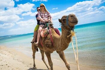 ein Paar reitet auf einem Kamel am Strand in Tunesien