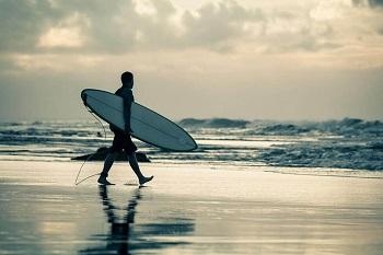 Surfer geht am Strand von Portugal zum Meer um zu surfen