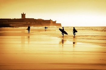 Einige Surfer gehen ins und aus dem Wasser am Strand von Portugal