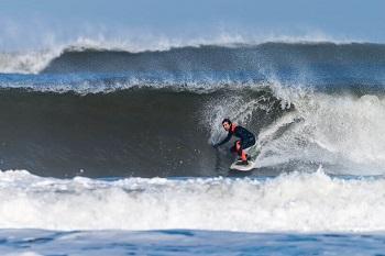 Surfer auf einer großen Welle am Strand von Portugal
