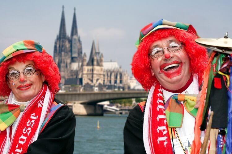 Kölner Jecken verkleidet als Clowns, im Hintergrund der Rhein und der Kölner Dom