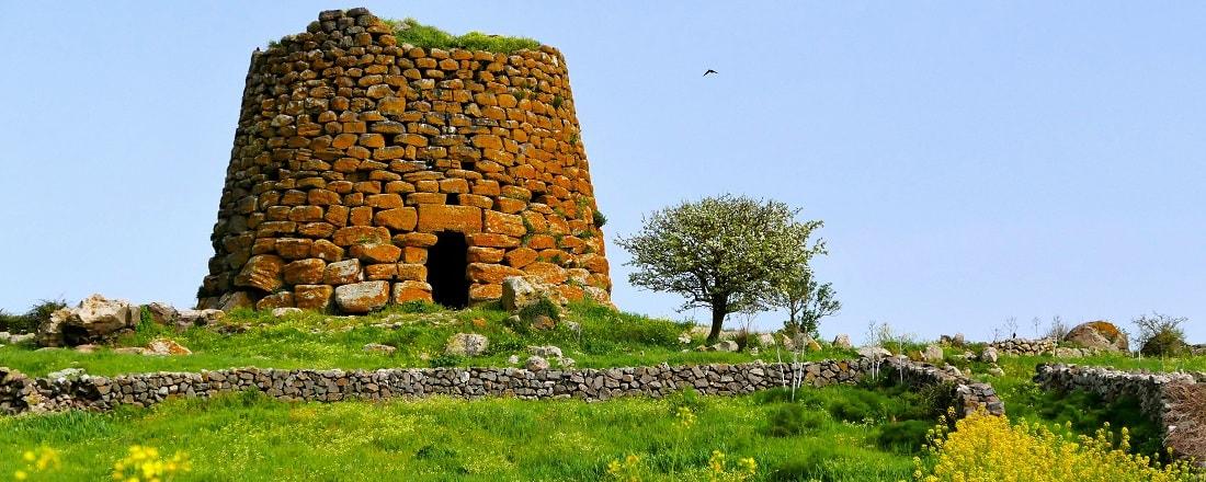 alter Steinturm auf einer grünen Wiese auf Sardinien, Nuraghe