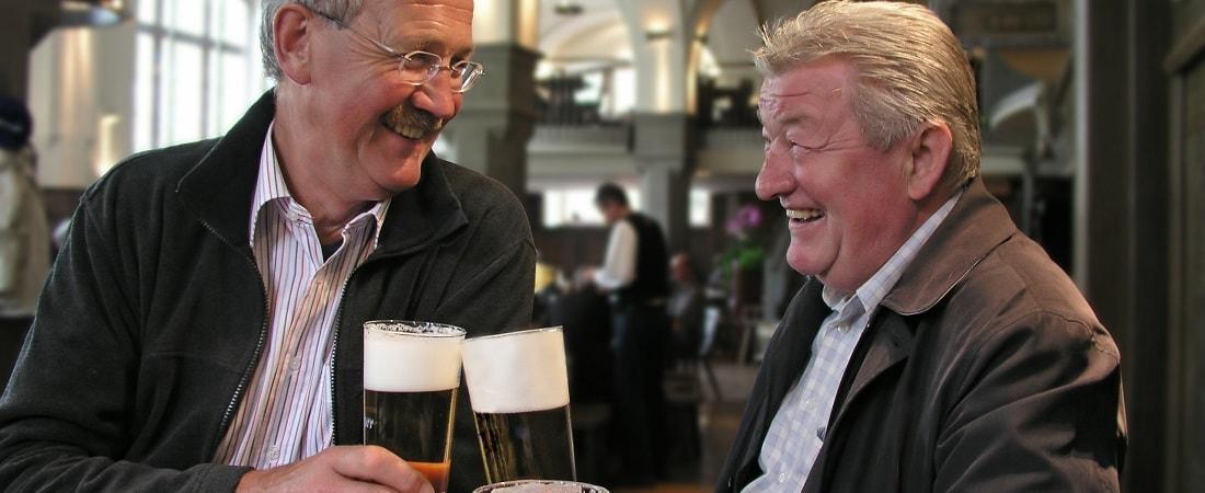 zwei ältere Herren stoßen mit Bier an